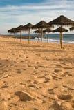 Détente sous la vue en bambou de parasol sur la plage sablonneuse dans le coucher du soleil de ciel bleu Photographie stock libre de droits