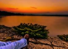 Détente sous un coucher du soleil orange au-dessus d'un lac calme Image libre de droits