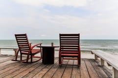 Détente sur la chaise de basculage et une tasse de café à la mer Images stock