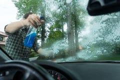 Détergent de pulvérisation sur une fenêtre Images stock
