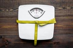 Détruisez le concept de poids Échelle et bande de mesure sur la vue supérieure de fond en bois foncé images stock