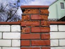 Détruit par le gel et la brique rouge d'humidité s'étendant après l'hiver photographie stock