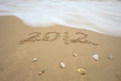 Dê boas-vindas ao ano novo 2012 escrevem na praia da areia Imagem de Stock