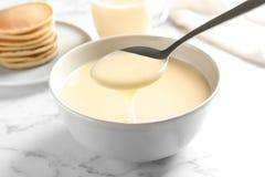 D? de derramar o leite condensado sobre a bacia na tabela de m?rmore, close up fotos de stock