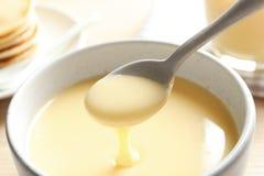 Dê de derramar o leite condensado sobre a bacia na tabela Produtos lácteos fotos de stock