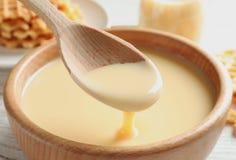Dê de derramar o leite condensado sobre a bacia na tabela Produtos lácteos foto de stock royalty free