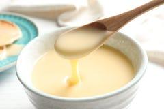 Dê de derramar o leite condensado sobre a bacia na tabela Produtos lácteos imagens de stock royalty free