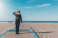 Día asoleado Visión posterior Turista de la mujer en un sombrero y con una mochila que se coloca en la costa y que mira el horizo Fotografía de archivo libre de regalías
