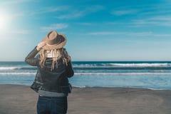 Día asoleado Visión posterior Turista de la mujer en un sombrero y con una mochila que se coloca en la costa y que mira el horizo Fotos de archivo libres de regalías