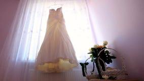 Día de boda el vestido del ` s de la novia cuelga en la ventana almacen de video
