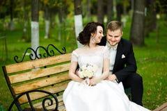 Día de boda: la novia y el novio hermosos se sientan en el banco en el parque Foto de archivo