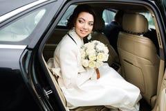 Día de boda: novia hermosa con el ramo de flores blancas en el coche Foto de archivo
