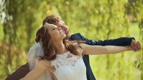 Día de boda Novio detrás de la novia debajo de los árboles verdes Abrace el vuelo en la luz del sol almacen de metraje de vídeo