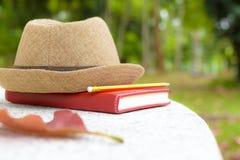 Día de fiesta, cuaderno y lápiz del concepto con el sombrero en la tabla blanca en parque público Fotos de archivo libres de regalías