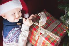 Día de fiesta de la Navidad Bebé en la caja de la abertura del sombrero de Papá Noel de regalos Imagen de archivo libre de regalías