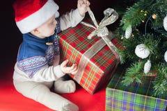 Día de fiesta de la Navidad Bebé en la caja de la abertura del sombrero de Papá Noel de regalos Fotos de archivo