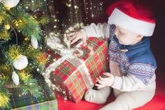 Día de fiesta de la Navidad Bebé en la caja de la abertura del sombrero de Papá Noel de regalos Foto de archivo