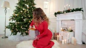 Día de fiesta de la Navidad, la muchacha mira juguetónamente los controles de la cámara en manos un regalo, retrato, Nochevieja,  almacen de metraje de vídeo
