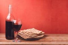 Día de fiesta del concepto de la pascua judía con la copa de vino y el matzoh en la tabla de madera sobre fondo rojo Fotografía de archivo libre de regalías