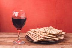 Día de fiesta del fondo de la pascua judía con la copa de vino y el matzoh en la tabla de madera Imagen de archivo libre de regalías