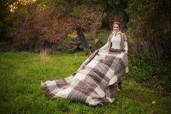 Día de fiesta del otoño La mujer joven sostiene la tela escocesa imagen de archivo