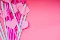 Día de fiesta del día de San Valentín pajas de beber rosadas brillantes con corazones y un fondo rosado del onpink de la cinta pa Imágenes de archivo libres de regalías