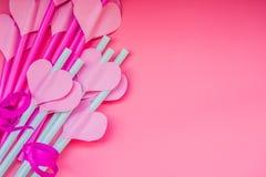 Día de fiesta del día de San Valentín pajas de beber rosadas brillantes con corazones y un fondo rosado del onpink de la cinta pa Foto de archivo