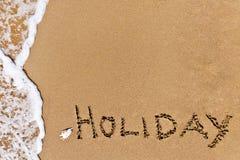 Día de fiesta escrito dibujado en la arena Foto de archivo