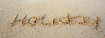 Día de fiesta escrito en arena en la playa Fotos de archivo libres de regalías