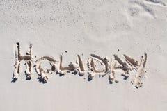 Día de fiesta escrito en la arena blanca Fotos de archivo libres de regalías