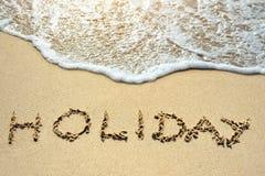 Día de fiesta escrito en la playa de la arena cerca del mar Foto de archivo