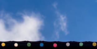 Día de fiesta feliz, concepto del fondo de la celebración del evento: línea de bombillas coloridas en los aleros del tejado que m Imagen de archivo libre de regalías