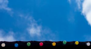 Día de fiesta feliz, concepto del fondo de la celebración del evento: línea de bombillas coloridas en los aleros del tejado que m Foto de archivo