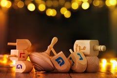 día de fiesta judío Jánuca con la colección de madera de los dreidels y x28; top& de giro x29; y luces de la guirnalda del oro en Imagen de archivo libre de regalías