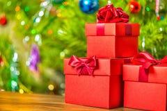 Día de fiesta de la Navidad del concepto de las cajas de regalo rojas con el arco en b de madera Fotos de archivo libres de regalías