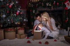 Día de fiesta de la Navidad La familia abre la caja mágica con el regalo fotos de archivo libres de regalías