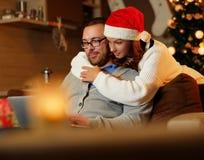 Día de fiesta de la Navidad Hembra en el sombrero del ` s de Papá Noel que abraza a un hombre que usa un ordenador portátil Fotografía de archivo