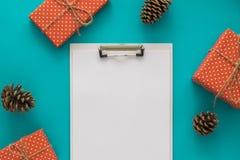 Día de fiesta de la Navidad y del Año Nuevo para hacer la lista con la libreta, cajas de regalo, cono del pino en el fondo azul M Foto de archivo libre de regalías
