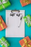 Día de fiesta de la Navidad y del Año Nuevo para hacer la lista con la libreta, pluma, cajas de regalo en el fondo azul Mofa para Fotos de archivo libres de regalías