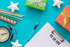 Día de fiesta de la Navidad y del Año Nuevo para hacer la lista con la libreta, pluma, cajas de regalo, reloj, tubos del cóctel,  Fotografía de archivo libre de regalías