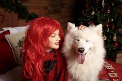 Día de fiesta y la Navidad del perro del invierno Una muchacha en un suéter hecho punto y con el pelo rojo con un animal doméstic Fotografía de archivo
