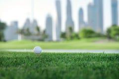 Día de golf La pelota de golf está en la camiseta para una pelota de golf en el gree Imagen de archivo libre de regalías