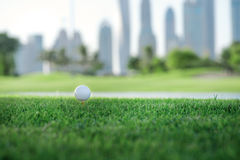 Día de golf La pelota de golf está en la camiseta para una pelota de golf en el gree Fotos de archivo libres de regalías