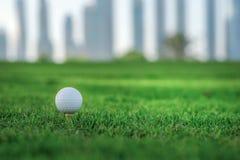 Día de golf La pelota de golf está en la camiseta para una pelota de golf en el gree Imagenes de archivo