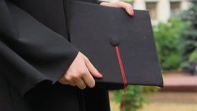 Día de graduación, estudiante en el vestido que sostiene el casquillo académico con la borla en manos almacen de metraje de vídeo