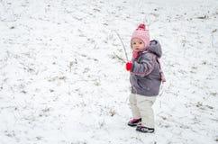 Día de invierno hermoso del pequeño bebé que juega en la nieve que agota una chaqueta encapuchada, los pantalones, el sombrero y  Fotografía de archivo