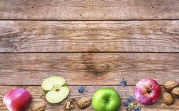 Día de la acción de gracias con las manzanas, las nueces y las bayas en un viejo fondo de madera Acción de gracias con las bayas  Fotos de archivo