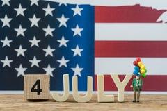 Día de la Independencia los E.E.U.U., viejo hombre de la gente miniatura que sostiene el globo w Fotografía de archivo libre de regalías