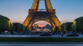 Día de la torre Eiffel al timelapse y a la gente de la noche que se sientan en la hierba por la tarde en París, Francia metrajes