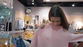 Día de las compras, la hembra feliz joven de los clientes elige la nueva ropa elegante en tienda de la moda durante descuentos en almacen de metraje de vídeo